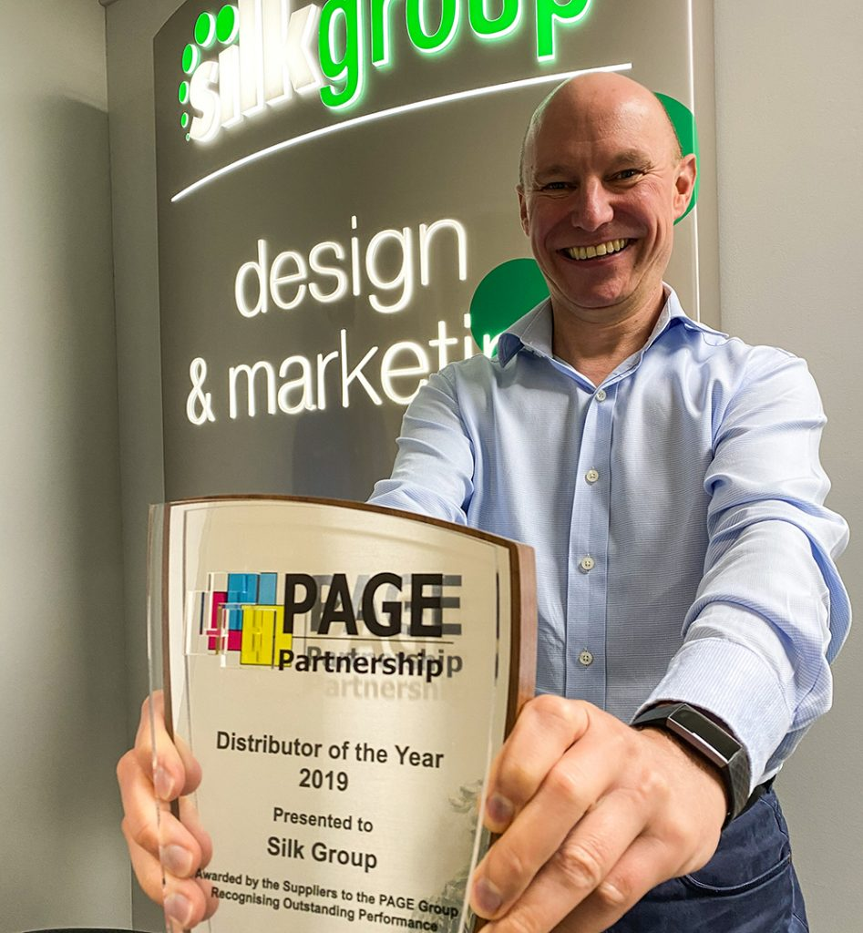 "Pete Slater holding the award from PAGE. Reading ""Distributor of the year 2019. Presented to Silk Group. Awarded by the suppliers to the PAGE group. Recognising outstanding performance."""